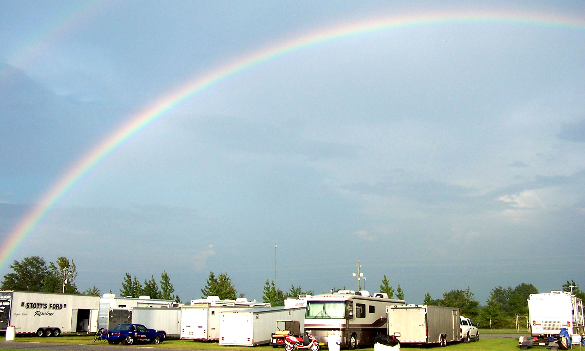 A rainbow in the sky above campers and a race car in a field