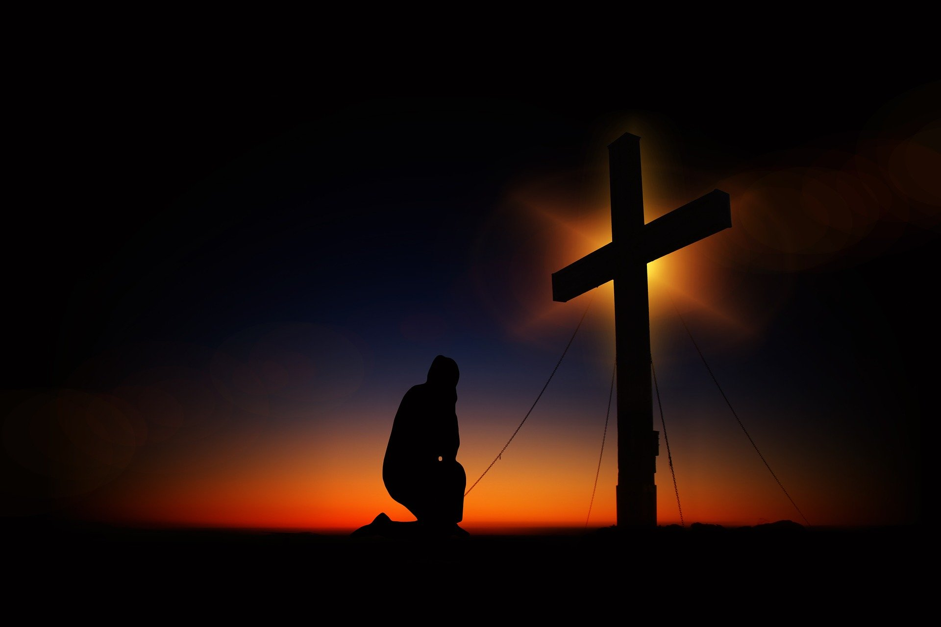 man kneeling at the cross after sunset