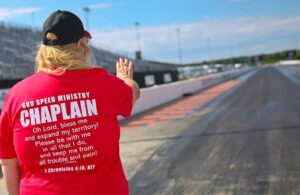 chaplain in red praying over race track